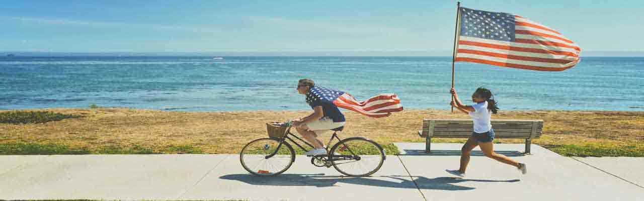 Man Riding Bike Followed by Running Girl with US Flag
