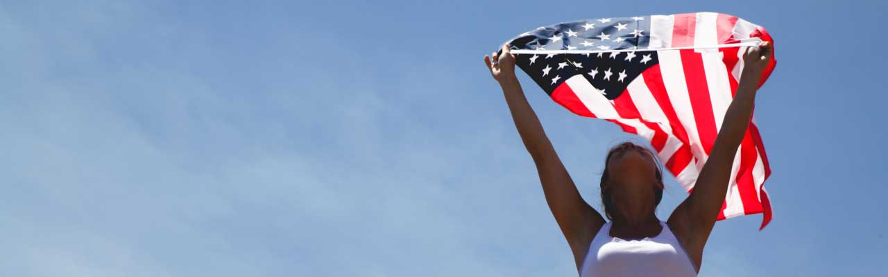 Woman Holding US Flag Against Sky